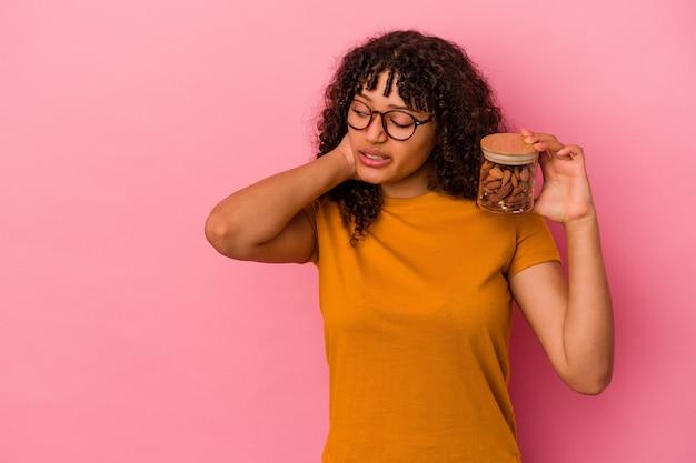 Jeune femme métisse tenant un pot d'amande isolé sur fond rose touchant l'arrière de la tête, pensant et faisant un choix.
