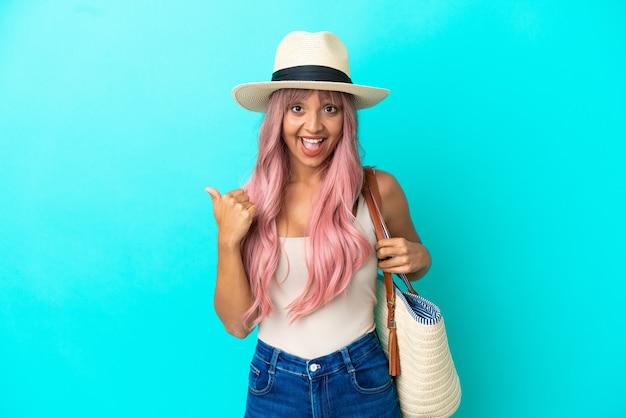 Jeune femme métisse tenant un sac de plage avec pamela isolé sur fond bleu pointant vers le côté pour présenter un produit