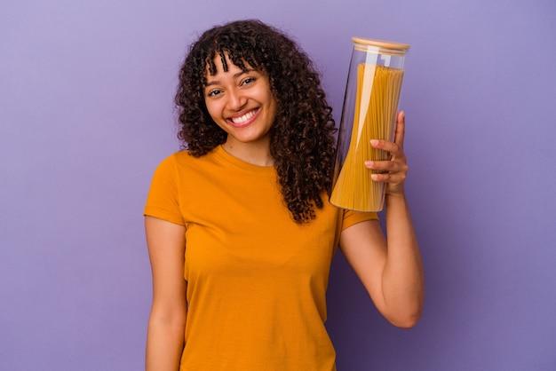 Jeune femme métisse tenant des spaghettis isolés sur fond violet heureux, souriant et joyeux.