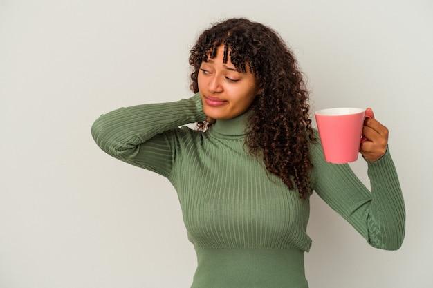Jeune femme métisse tenant une tasse isolée sur fond blanc touchant l'arrière de la tête, pensant et faisant un choix.