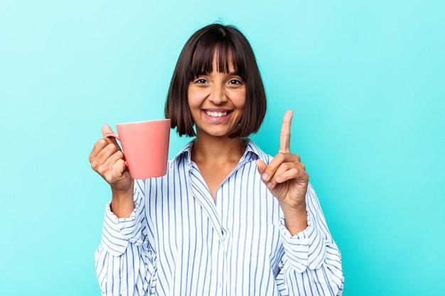 Jeune femme métisse tenant une tasse rose isolée sur fond bleu montrant le numéro un avec le doigt.