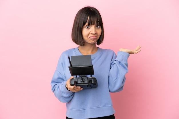 Jeune femme métisse tenant une télécommande de drone isolée sur fond rose ayant des doutes en levant les mains