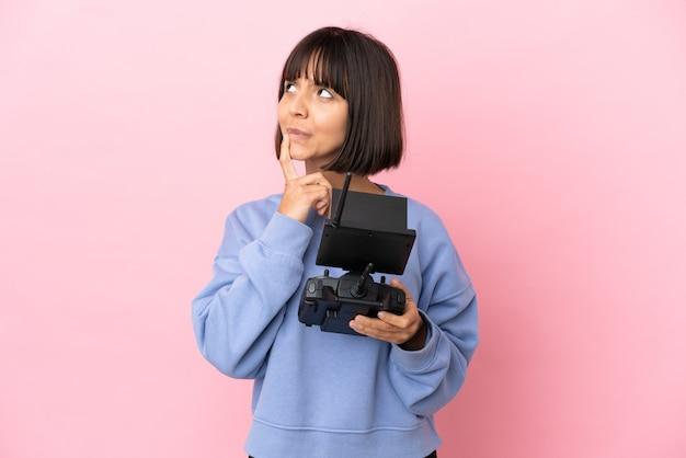 Jeune femme métisse tenant une télécommande de drone isolée sur fond rose ayant des doutes en levant les yeux