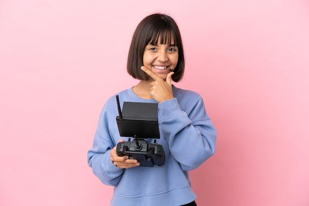 Jeune femme métisse tenant une télécommande de drone isolée sur fond rose heureux et souriant