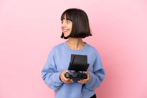 Jeune femme métisse tenant une télécommande de drone isolée sur fond rose regardant sur le côté et souriant