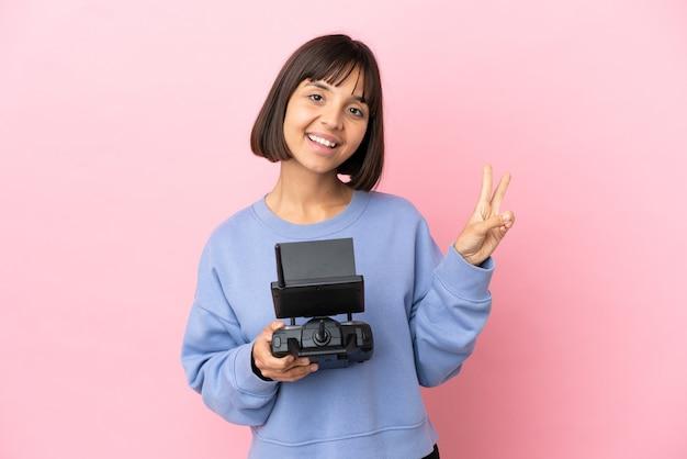 Jeune femme métisse tenant une télécommande de drone isolée sur fond rose souriant et montrant le signe de la victoire