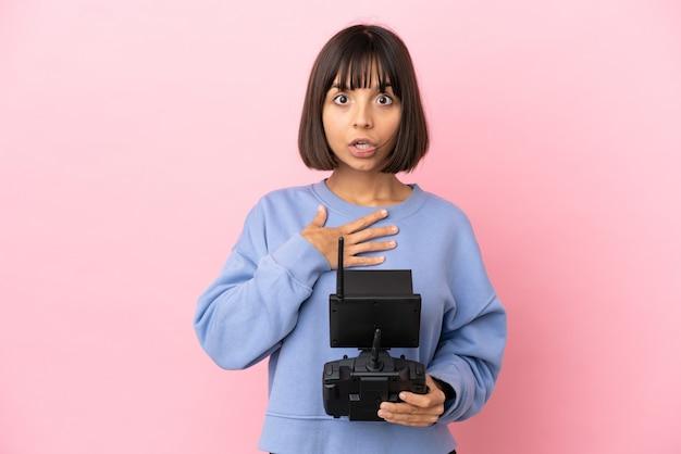Jeune femme métisse tenant une télécommande de drone isolée sur fond rose surpris et choqué en regardant à droite