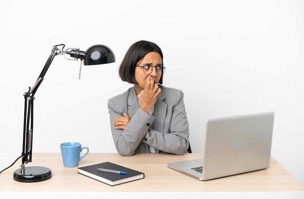 Jeune femme métisse travaillant au bureau est un peu nerveuse
