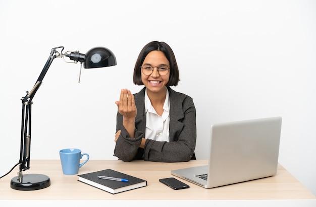 Jeune femme métisse travaillant au bureau invitant à venir avec la main. heureux que tu sois venu