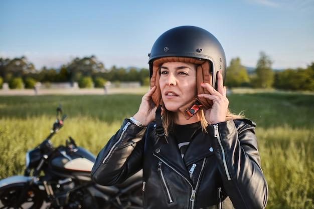 Jeune femme mettant le casque de moto