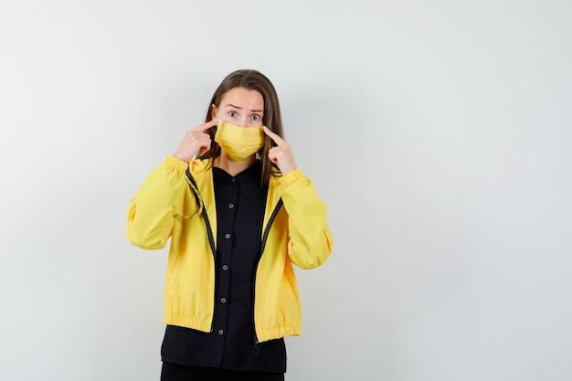 Jeune femme mettant l'index sur les joues