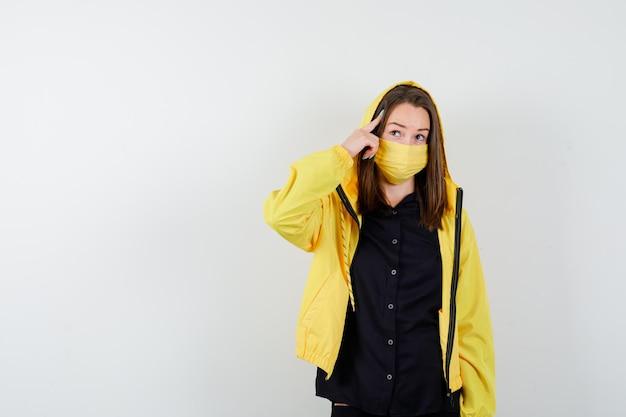 Jeune femme mettant l'index sur la tempe et à la pensive