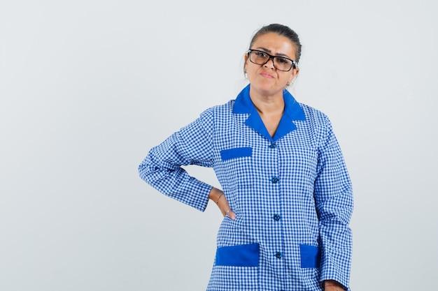Jeune femme mettant la main sur la taille et portant des lunettes en chemise de pyjama vichy bleu et à la jolie, vue de face.