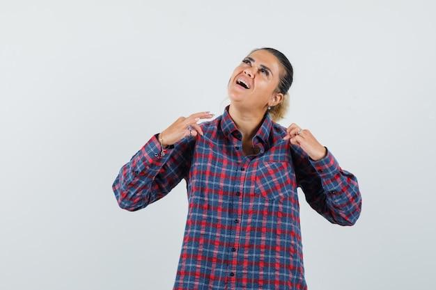 Jeune femme mettant les mains sur la chemise en chemise à carreaux et à la vue de face, heureux.