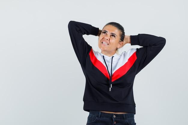Jeune femme mettant les mains derrière la tête en pull et jeans noirs et à la pensif. vue de face.