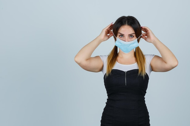 Jeune femme mettant un masque de protection