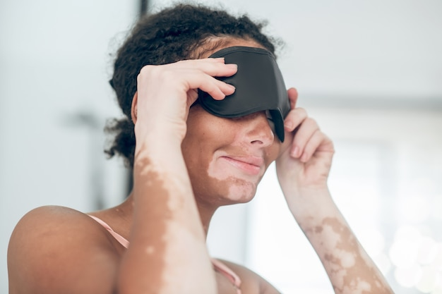 Une jeune femme mettant un masque de sommeil
