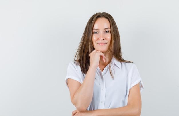 Jeune femme mettant sa main sur le menton en chemisier blanc et à la confiance