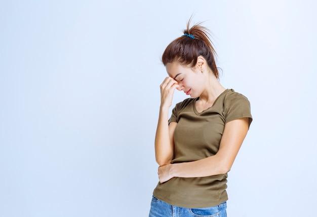 Jeune femme mettant son poing sur son front