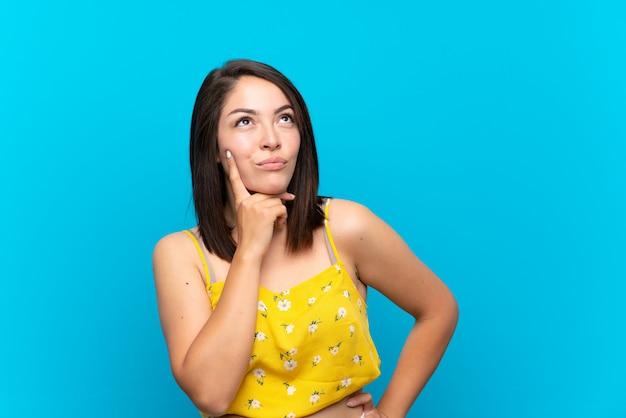 Jeune femme mexicaine sur bleu isolé, pensant une idée