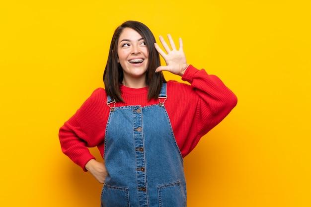 Jeune femme mexicaine avec une combinaison sur un mur jaune, écoutant quelque chose en mettant la main sur l'oreille