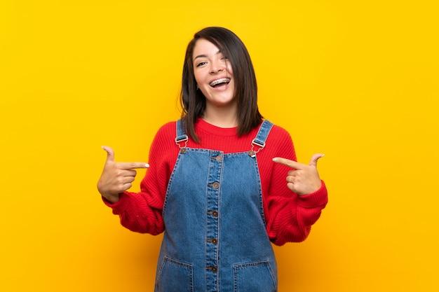 Jeune femme mexicaine avec une combinaison sur un mur jaune fière et satisfaite