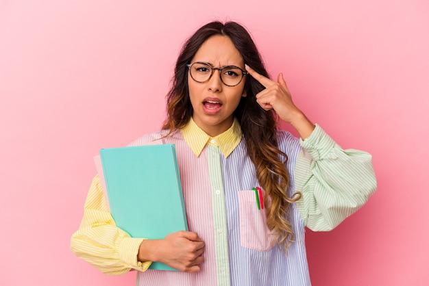 Jeune femme mexicaine étudiante isolée sur fond rose montrant un geste de déception avec l'index.