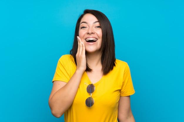 Jeune femme mexicaine sur fond bleu isolé avec une expression faciale surprise et choquée