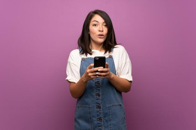 Jeune femme mexicaine sur fond isolé à l'aide de téléphone portable