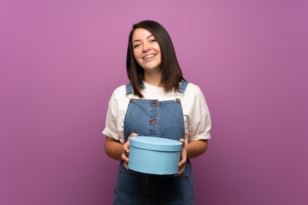 Jeune femme mexicaine sur fond isolé, tenant une boîte-cadeau