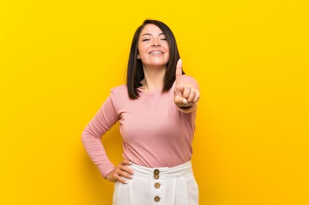 Jeune femme mexicaine sur fond jaune isolé montrant et en levant un doigt