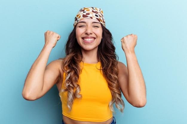 Jeune femme mexicaine isolée sur fond bleu acclamant insouciante et excitée. notion de victoire.