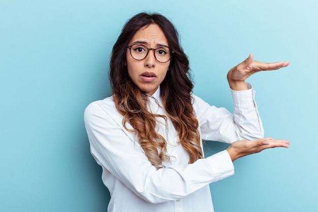 Jeune femme mexicaine isolée sur fond bleu choquée et étonnée tenant un espace de copie entre les mains.