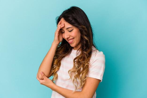 Jeune femme mexicaine isolée sur fond bleu clignote à l'appareil photo à travers les doigts, gêné couvrant le visage.