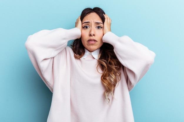 Jeune femme mexicaine isolée sur fond bleu couvrant les oreilles avec les mains essayant de ne pas entendre un son trop fort.