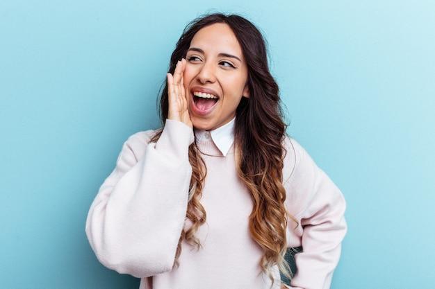 Jeune femme mexicaine isolée sur fond bleu criant excitée à l'avant.