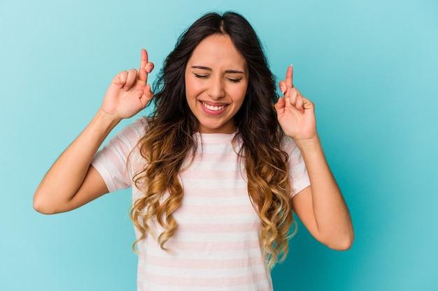 Jeune femme mexicaine isolée sur fond bleu croisant les doigts pour avoir de la chance