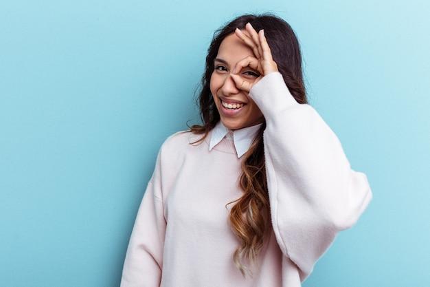 Jeune femme mexicaine isolée sur fond bleu excitée en gardant un geste ok sur les yeux.