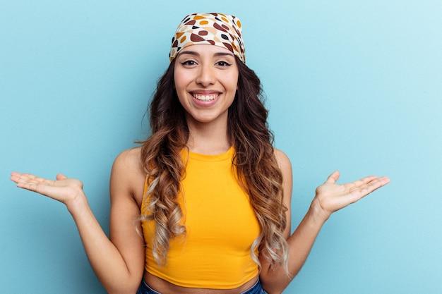 Une jeune femme mexicaine isolée sur fond bleu fait de l'échelle avec les bras, se sent heureuse et confiante.