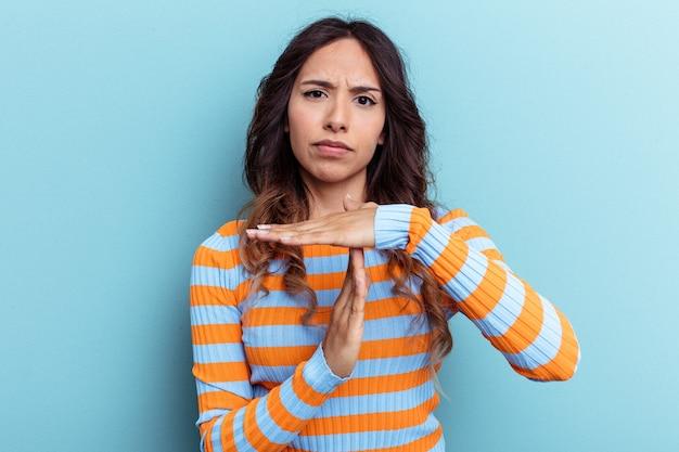 Jeune femme mexicaine isolée sur fond bleu montrant un geste de délai d'attente.