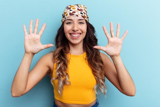 Jeune femme mexicaine isolée sur fond bleu montrant le numéro dix avec les mains.