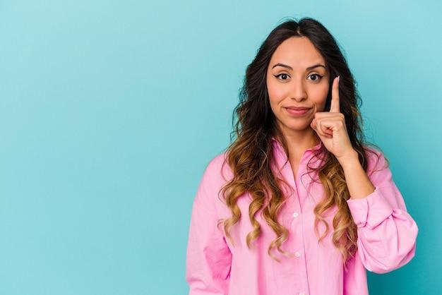 Jeune femme mexicaine isolée sur fond bleu montrant le numéro un avec le doigt.