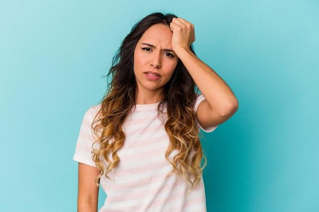 Jeune femme mexicaine isolée sur fond bleu oubliant quelque chose, giflant le front avec la paume et fermant les yeux.