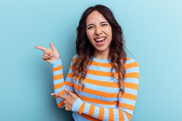 Jeune femme mexicaine isolée sur fond bleu pointant avec les index vers un espace de copie, exprimant l'excitation et le désir.
