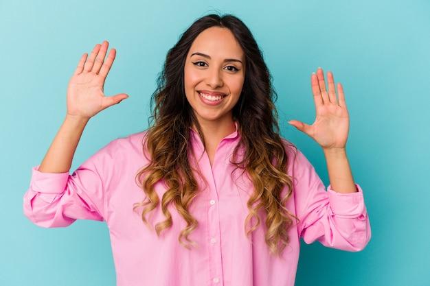 Jeune femme mexicaine isolée sur fond bleu recevant une agréable surprise, excitée et levant les mains.