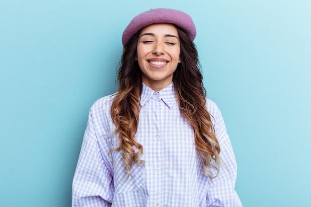Jeune femme mexicaine isolée sur fond bleu rit et ferme les yeux, se sent détendue et heureuse.