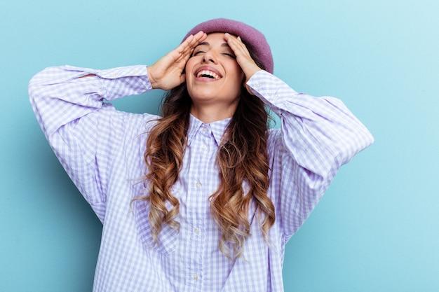 Jeune femme mexicaine isolée sur fond bleu rit joyeusement en gardant les mains sur la tête. notion de bonheur.