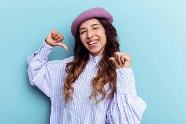 Jeune femme mexicaine isolée sur fond bleu se sent fière et confiante, exemple à suivre.