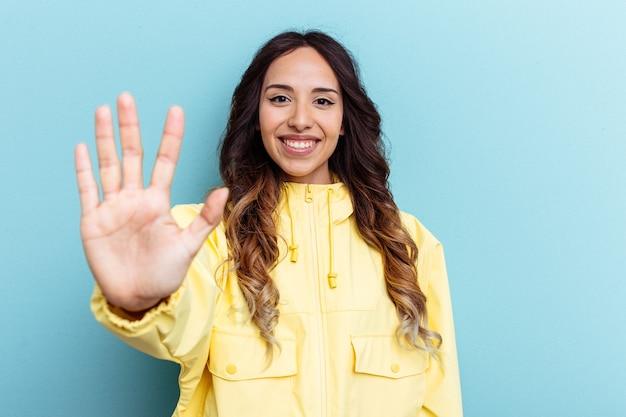 Jeune femme mexicaine isolée sur fond bleu souriant joyeux montrant le numéro cinq avec les doigts.