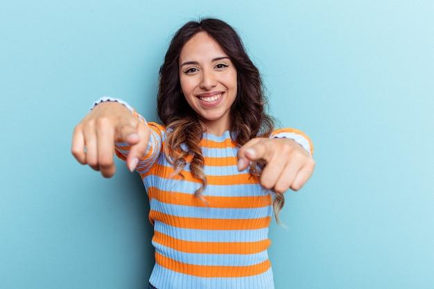 Jeune femme mexicaine isolée sur fond bleu, sourires joyeux pointant vers l'avant.
